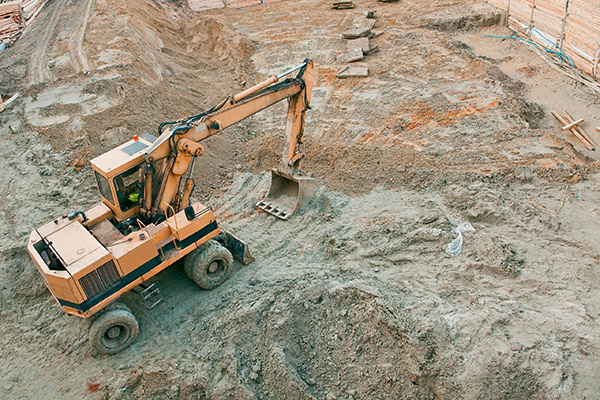 An excavator construction machine in the middle of a dirt construction site.