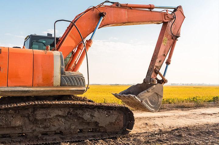 Orange excavator driving on dirt road