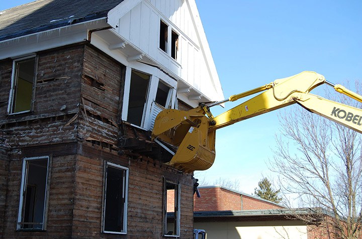Old home being demolished with an excavator machine.
