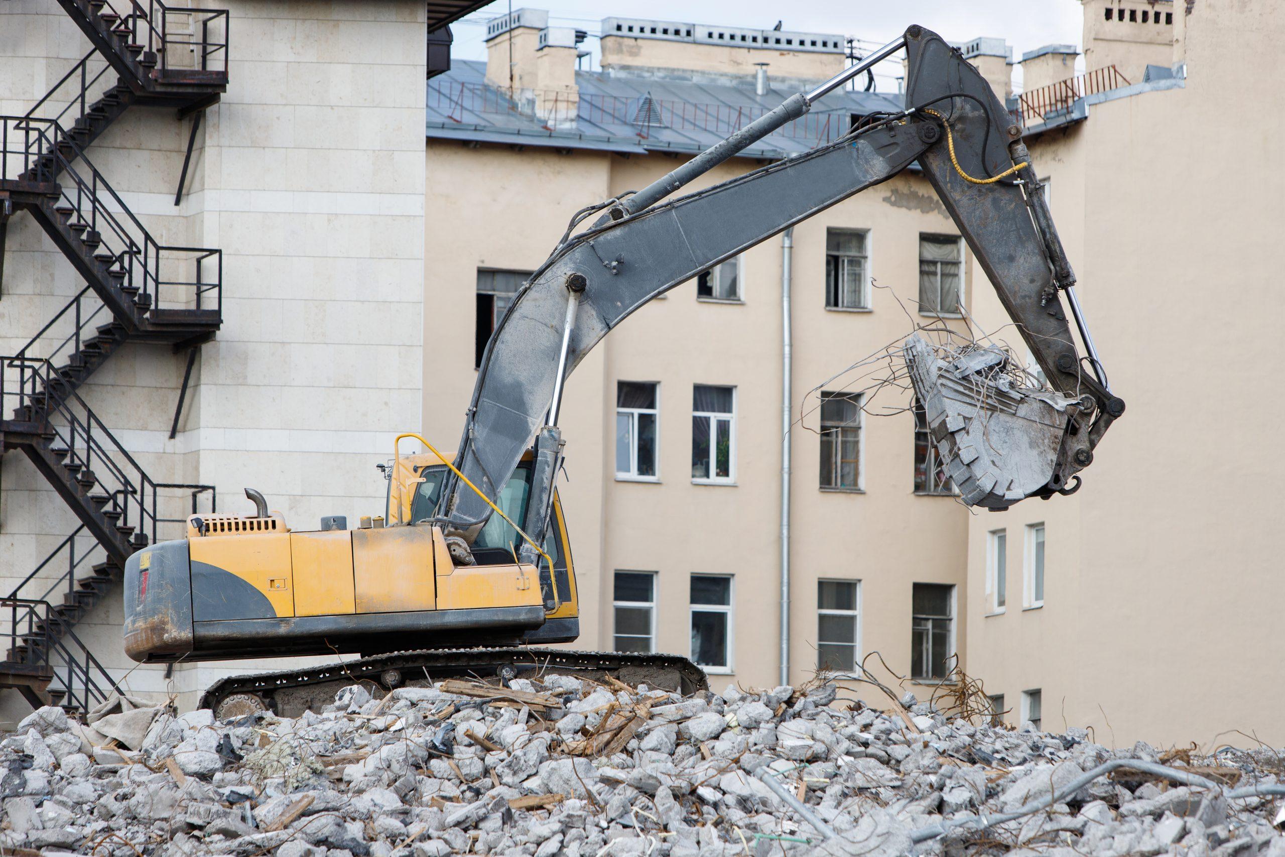 Excavating machine on demolition site driving on pile of broken concrete.