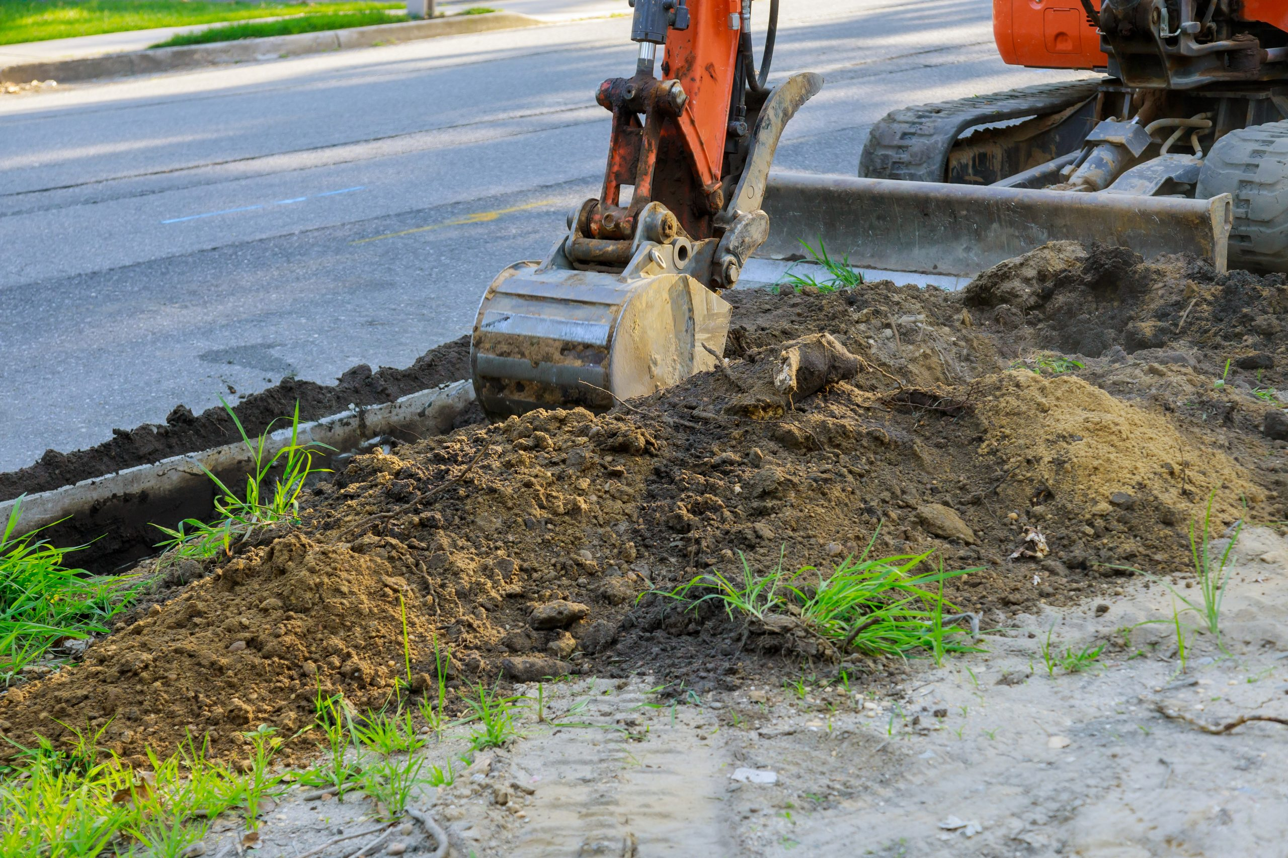 Construction worker using special machine to create trench in residential area.