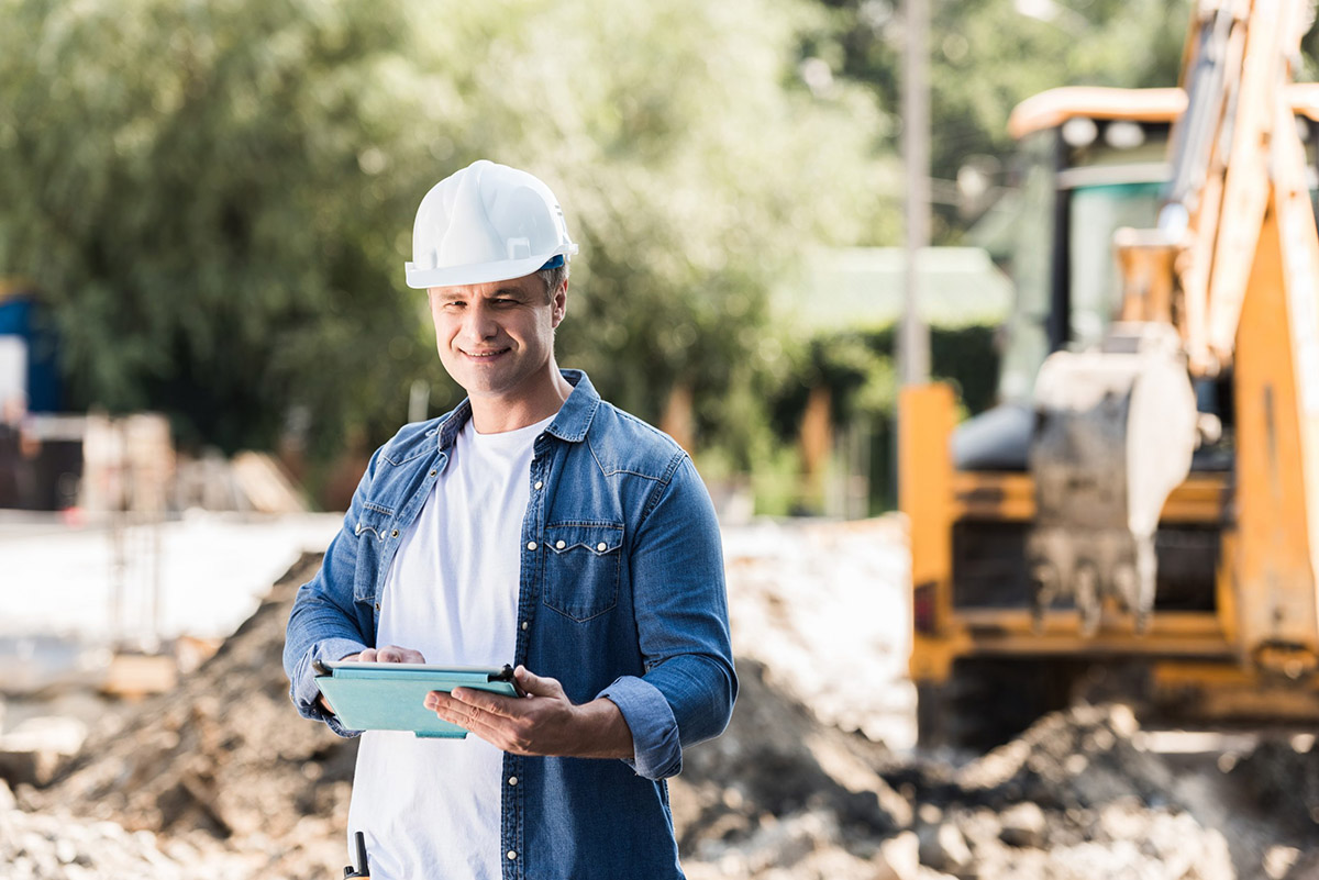 handsome-mature-construction-worker-with-tablet-QCNY2LV-scaled