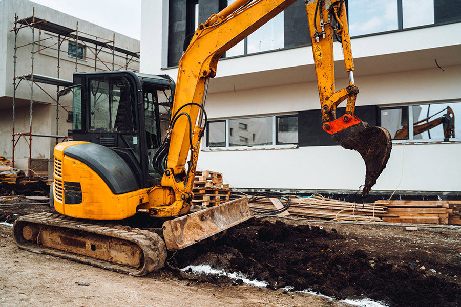Excavating machine digging a hole for residential construction purposes.