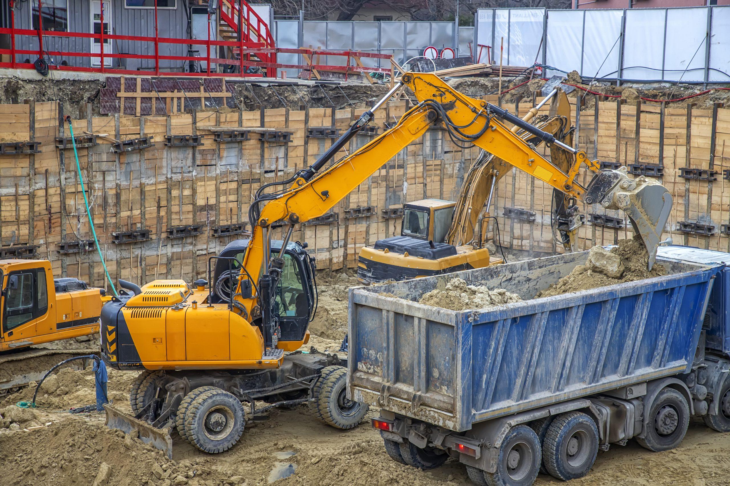 Excavator placing debris in dump truck.