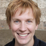 Woman with short red hair and blue eyes smiling at the camera.